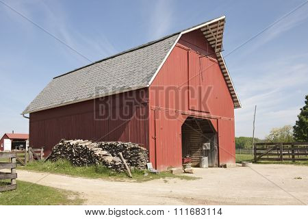 A red storage barn with an opened barn door on a bright, sunny day.  Stacks of wood leans against one side, a distant barn and rail fences on all sides, near and far.