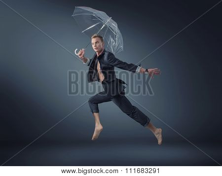 Sporty businessman holding an umbrella