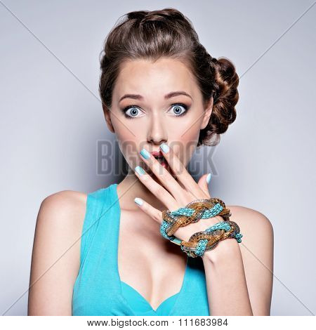 Young beautiful woman with jewelry. Girl Fashion  in blue dress . Attractive model with blue nails.