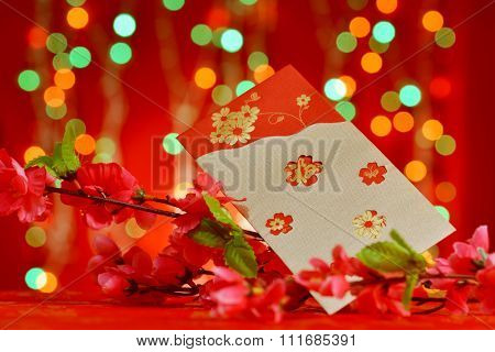 Chinese new year decorations, red packet and plum flower on red glitter background.