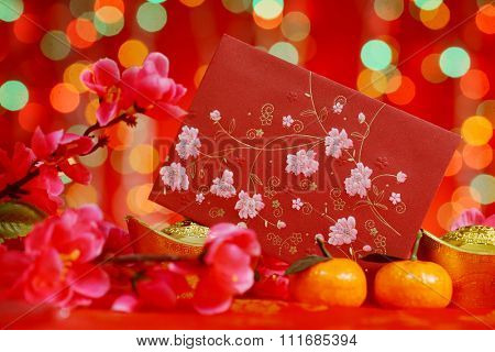Chinese new year festival decorations, red packet, mandarin orange and plum blossom on red glitter background.