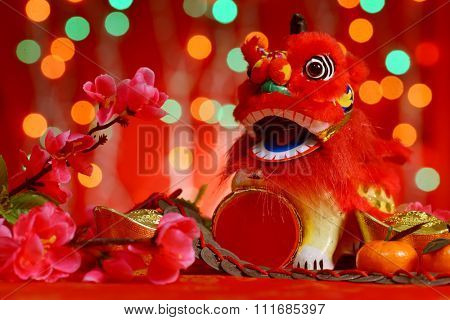 Chinese new year festival decorations, miniature dancing lion and ancient money on red glitter background.