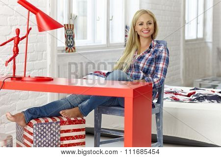 Cheerful young woman sitting at desk at home, smiling happy.