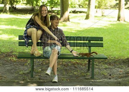 A young couple hand-feed a squirrel on a Park bench.
