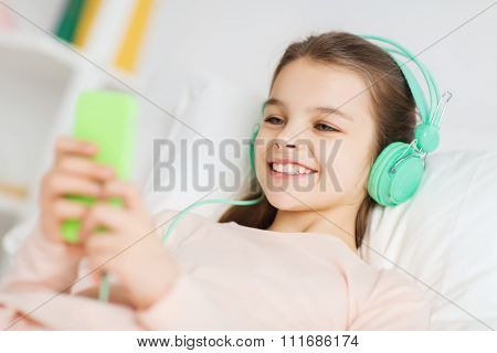 people, children, rest, and technology concept - happy smiling girl lying awake with smartphone and headphones in bed listening to music at home