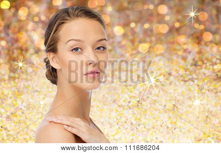 beauty, people, body care and health concept - smiling young woman face and hand on bare shoulder over golden glitter background