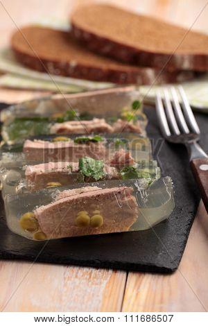 Beef tongue aspic on a slate cutting board