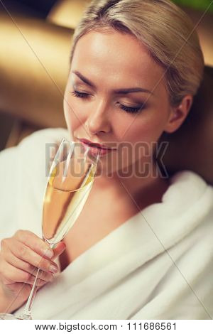 people, beauty, lifestyle, holidays and relaxation concept - beautiful young woman in white bath robe drinking champagne at spa