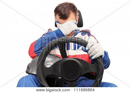 Disappointed car racer sitting on a car seat and looking down isolated on white background