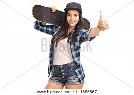Young cheerful female skater holding a skateboard and giving a thumb up isolated on white background