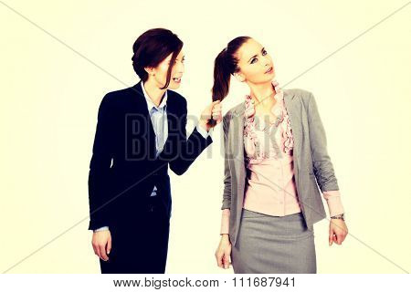 Frustrated businesswoman pulls her friends hair.