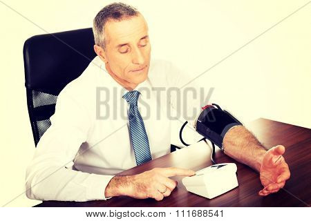 Above view businessman measuring blood pressure.