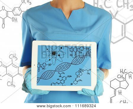 Young doctor holding tablet-pc with DNA molecule on screen