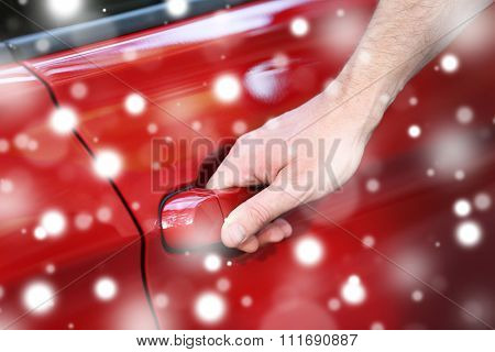 Male hand holding the door handle of red car over snow effect