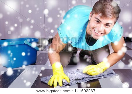 Young man cleaning floor in room over snow effect