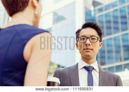 Business people having a talk while walking in a businesss district