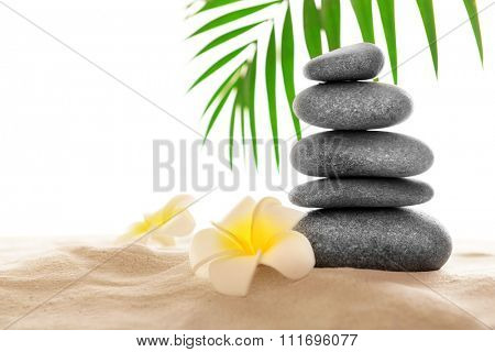 Few spa stones with plumeria on sand, isolated on white