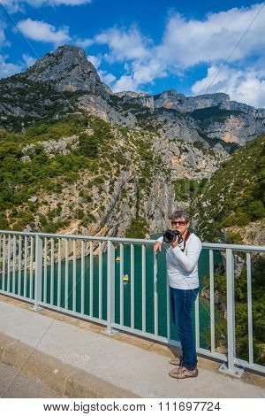 Travel to Provence. An elderly woman with a camera on a bridge over the River Verdon