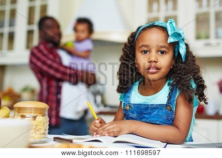 Adorable African-American girl looking at camera while doing home assignment in the kitchen