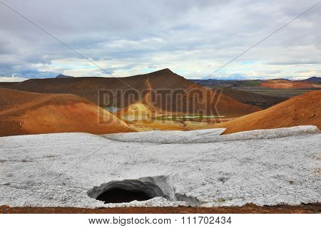 July in Iceland. Krafla lake in the crater of an extinct volcano. On the banks are last year's snow fields