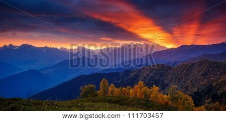 Fantastic red sunbeams with overcast sky at the foot of Mt. Ushba. Dramatic morning scene. Location Upper Svaneti, Mestia, Georgia, Europe. High Caucasus ridge. Warm toning effect. Beauty world.