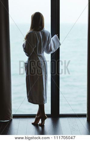 Back view of beautiful slim female standing on tiptoe near the panoramic window