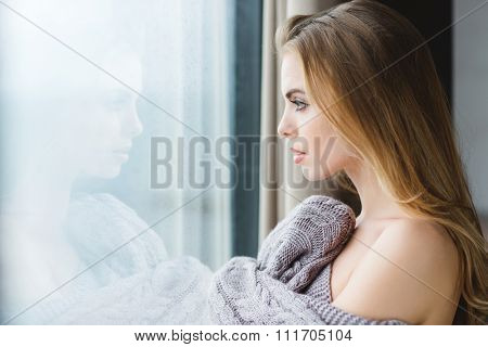 Profile of beautiful young woman in grey knitted coverlet looking out of the window