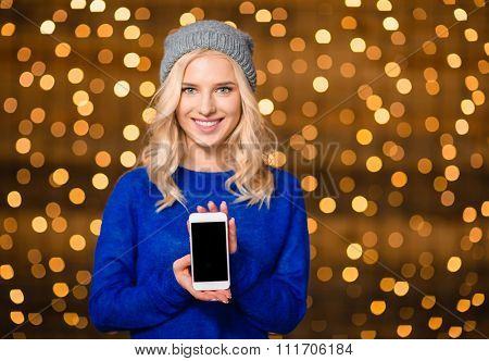 Portrait of a smiling woman showing blank smartphone screen over holdays lights background
