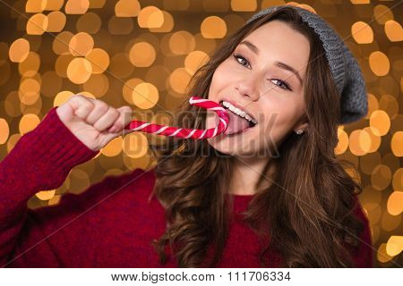 Beautiful happy woman in red sweater and grey hat eating candy cane over shining background