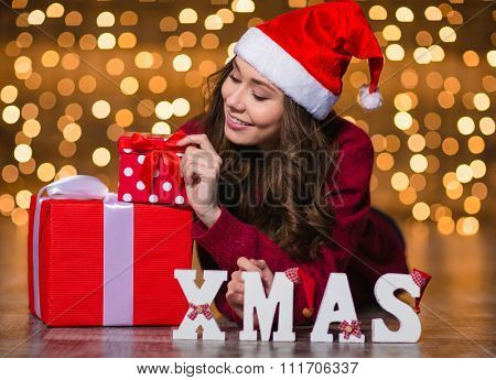 Attractive smiling young woman lying near white letters spelling word Xmas and present boxes over shining background