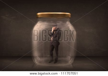 Businessman shut into a glass jar concept on background