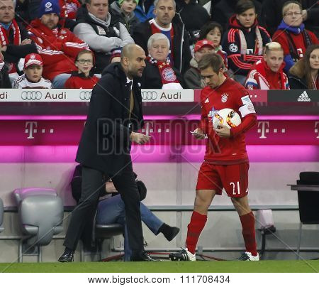 MUNICH, GERMANY - DECEMBER 12 2015: Josep Guardiola manager of Bayern Munich hands captain Philipp Lahm a note during the Bundesliga match between Bayern Muenchen and FC Ingolstadt