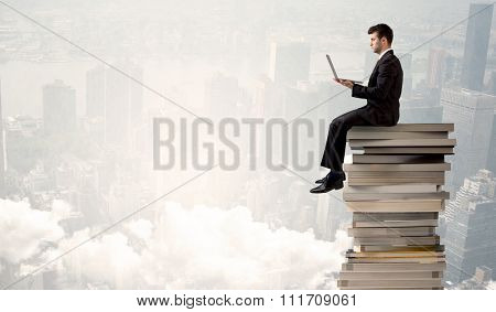 A serious businessman with laptop tablet in elegant suit sitting on a stack of books in front of cityscape