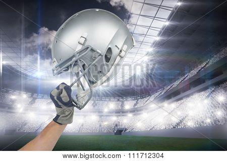 American football player handing his helmet against sports arena