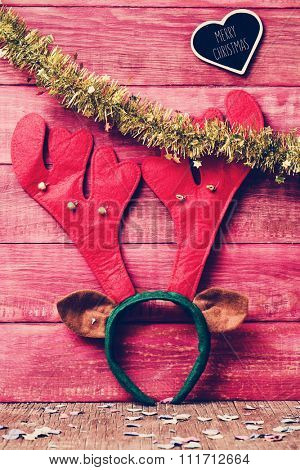 closeup of a reindeer antler headband on a red rustic wooden background ornamented with golden tinsel and a heart-shaped chalkboard with the text merry christmas written in it