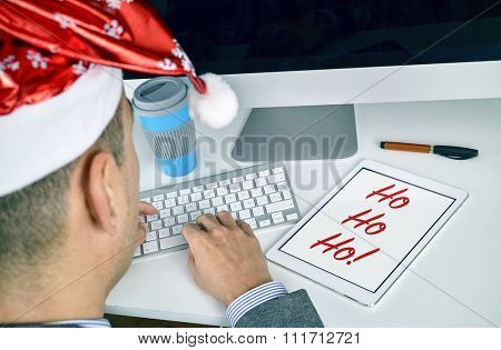 closeup of a young caucasian businessman wearing a santa hat, sitting at his office desk, with a tablet with text ho ho ho in its screen
