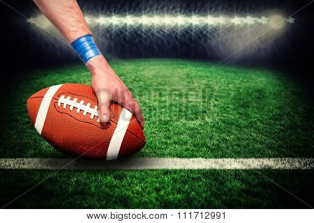 American football player placing the ball against rugby pitch