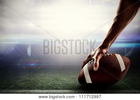 Cropped image of sports player holding ball against american football arena