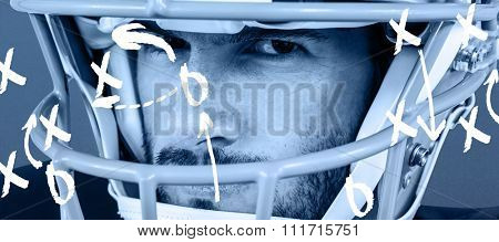 Close-up portrait of stern American football player against blue background