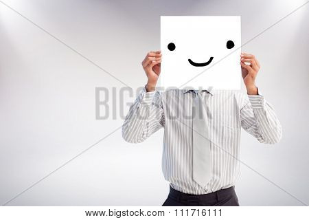 Businessman holding a white card covering his face against grey background