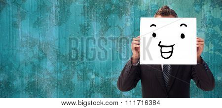 Businessman holding a white card in front of his face against blue paint splashed surface