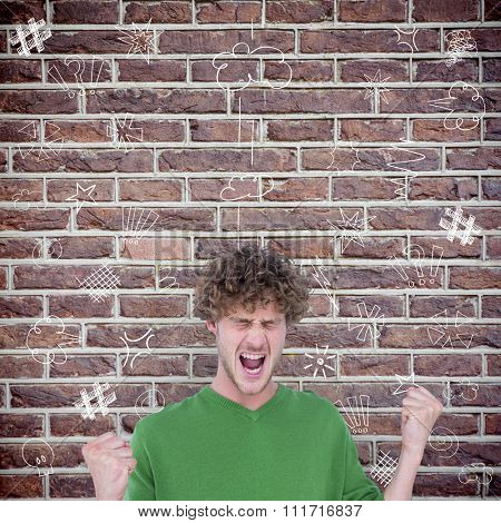 Furious man screaming with clenched fists against red brick wall