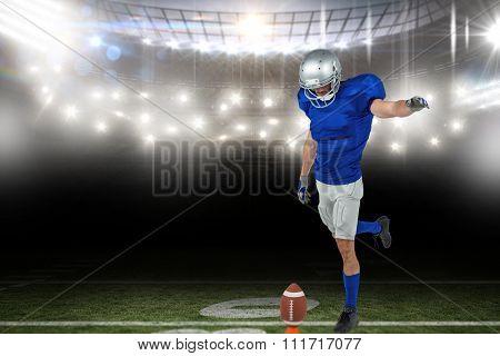 American football player kicking ball against american football arena
