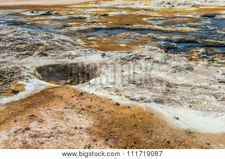 Mudpot in the geothermal area Hverir, Iceland. The area around the boiling mud is multicolored and cracked.
