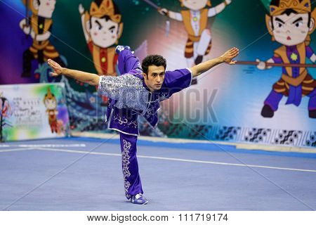 JAKARTA, INDONESIA - NOVEMBER 17, 2015: Reza Khalif Zadeh of Iran performs the movements in the men's Compulsory Changquan event in the 13th World Wushu Championship 2015 in Istora Senayan Stadium.