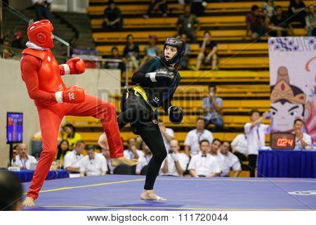 JAKARTA, INDONESIA - NOVEMBER 17, 2015: Shahrbano Semiromi of Iran (red) fights Delphine Stambouli of France (black) in the women's 65kg Sanda event at the 13th World Wushu Championship 2015.