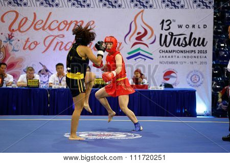 JAKARTA, INDONESIA - NOVEMBER 17, 2015: Ling Ling Liu of China (red) fights Maristein Nascimento of Brazil (black) in the women's 56kg Sanda event at the 13th World Wushu Championship 2015.