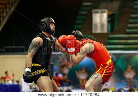 JAKARTA, INDONESIA - NOVEMBER 17, 2015: Domenico Stabile of Italy (red) fights Georges Eid of Lebanon in the men's 80kg Sanda event at the 13th World Wushu Championship 2015.