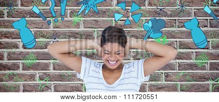 Angry woman covering ears against red brick wall
