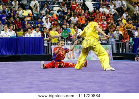 JAKARTA, INDONESIA - NOVEMBER 17, 2015: The Malaysia's women's duel team performs the action fights in the Women's Duel event at the 13th World Wushu Championship 2015 in Istora Senayan Stadium.